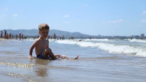 A little boy sitting on the sand in the water Footage