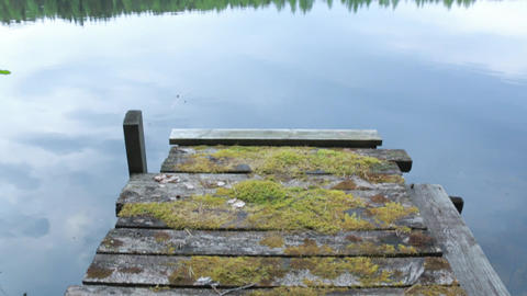 Tilt Shot Of Old Wooden Dock And Distant Shore stock footage