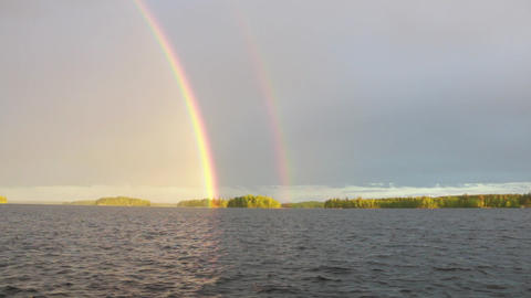 Panning shot of rainbow over lake Live Action