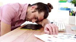 Overworked graphic designer sleeping on his desk Footage