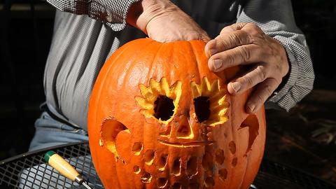 Man finishing up Halloween pumpkin Footage