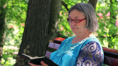 Elderly woman reading bible outdoors Footage