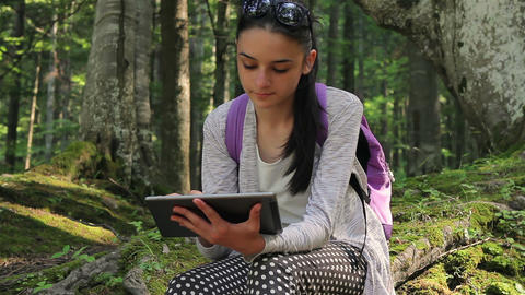 Tourist girl using a tablet pc in the forest Live Action