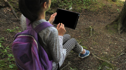 Young girl using a tablet pc in the forest Live Action