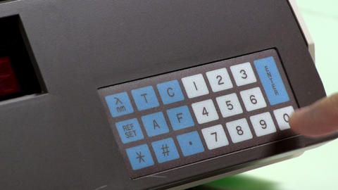 Enter keypad numbers in lab equipment Footage