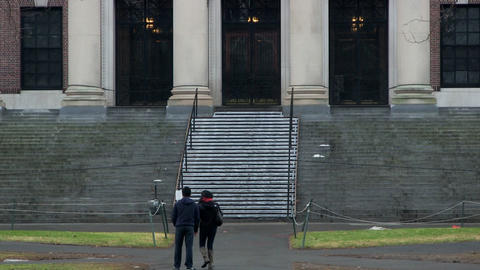 Two college students in front of Harvard library Footage