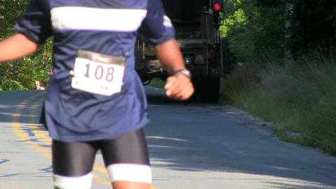 Triathlon runners pass water station; 15 Footage