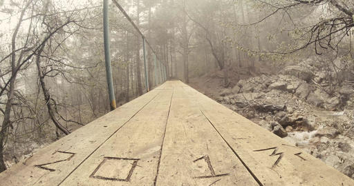 wooden bridge over a mountain river in a pine forest in the fog Footage