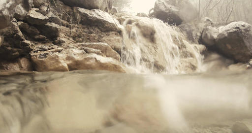 view from the surface of a small puddle beneath a small beige rock waterfall Footage