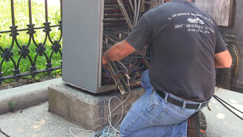 A city worker repairing a traffic control panel on sidewalk during hot summer da Footage
