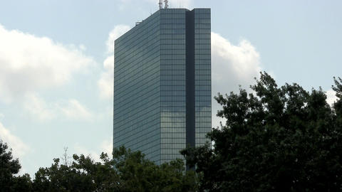 John Hancock building in Boston stands against blue sky and clouds with trees in Footage