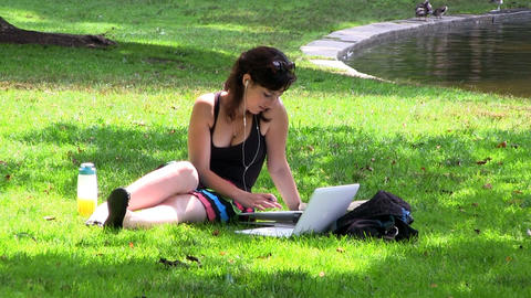 A pretty female college student sits in shade on grass near pond at Boston publi Footage