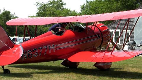 Passengers boarding a red biplane at airfield for aerial tour of Cape Cod and th Footage