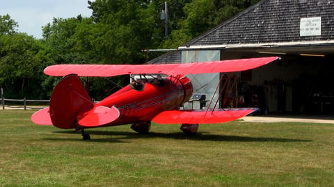 Red biplane starts to taxi to runway at airfield to take passengers on tour of C Footage