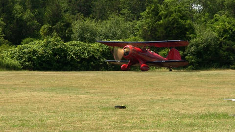 Red biplane waits at start of runway at airfield making last minute checks befor Footage