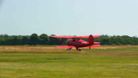 Red biplane takes off at Cape Cod Airfield taking passengers on tour of Cape Cod Footage