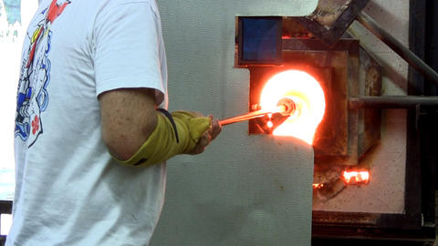 Glass artist heating vase on end of blowpipe while rotating in gas furnace. He w Footage