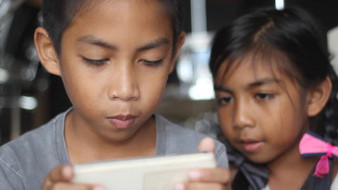 Brother and sister having fun with game in smartphone Live Action