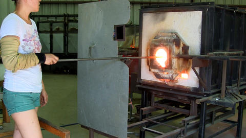 A Japanese gaffer stands behind her heat shield in front of gas furnace as she r Footage