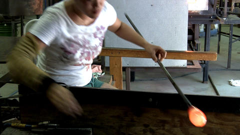 A Japanese glass artist blows into end of pipe to change shape of gather as she  Footage