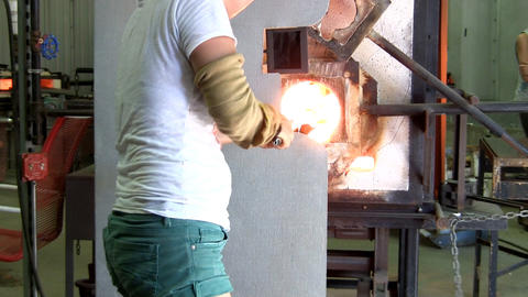 Glass artist reheats gather on pipe then blows air into one end like a balloon t Footage