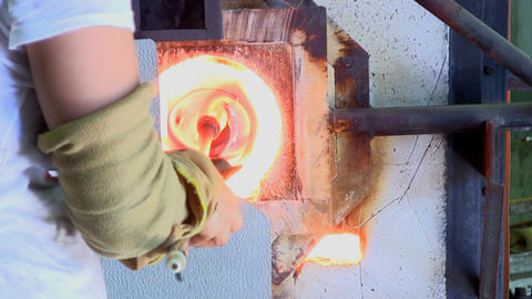 Glass artist reheats mouth of multicolored vase in gas furnace Footage