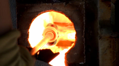 Chunks of colored glass being melted on end of blowpipe inside glory hole of gas Footage