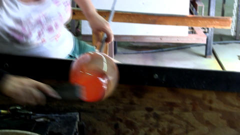 Flattening base of vase with wooden paddle as glass artist rolls blowpipe across Footage