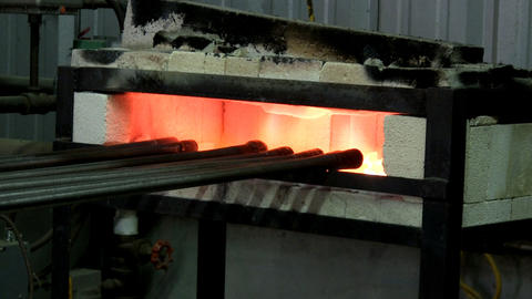 A pipe heating gas furnace keeps row of punties hot for use in glass work Footage