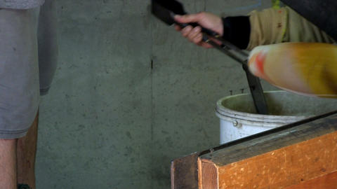 Japanese glass artist sits and workbench using tweezers to open mouth of vase. S Live Action