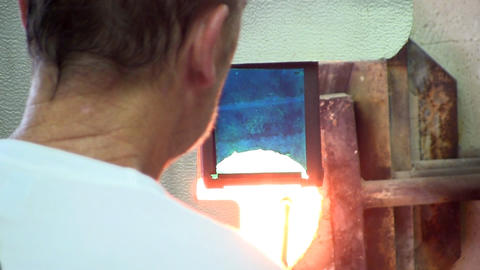 Gaffer stands behind heat shield at gas furnace while reheating his work. He vie Footage