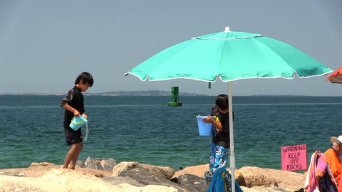 Two young boys have fun dumping pales of water onto rocks at Menemsha beach on M Footage