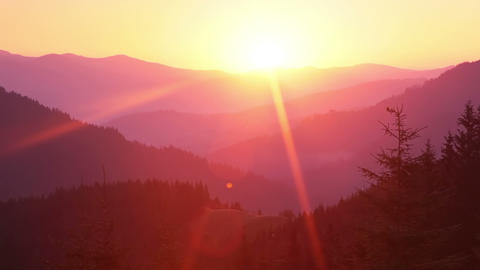 Sunrise over the Forested Mountains and Sunrays. Time Lapse Footage