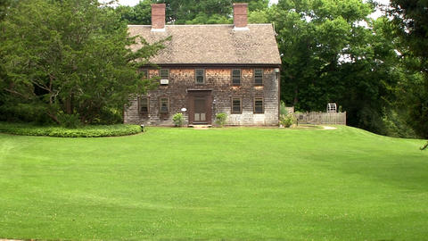 A vintage antique colonial home sits on hill of manicured lawn at Heritage Plant Footage