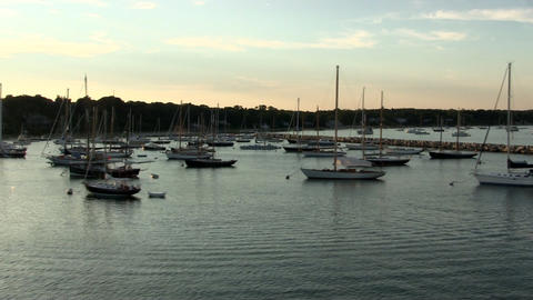 Sailboats moored and anchored in Vineyard Haven as sun sets from deck of ferry b Footage