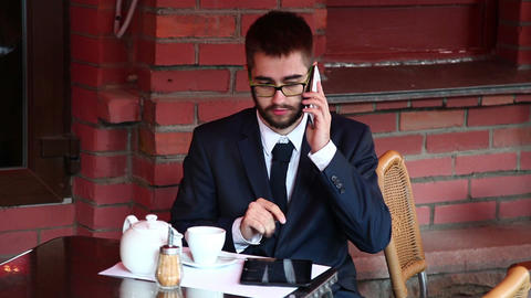 Attractive man on the phone in a cafe. Dolly Shot Footage