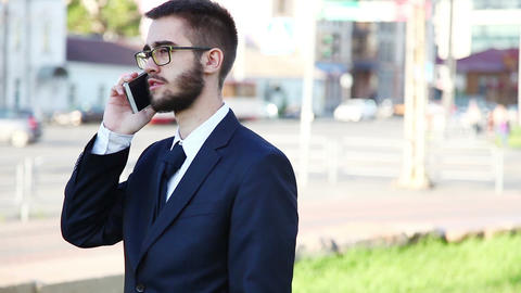 Young Businessman Talking On Mobile Phone In The City. Dolly Shot Footage