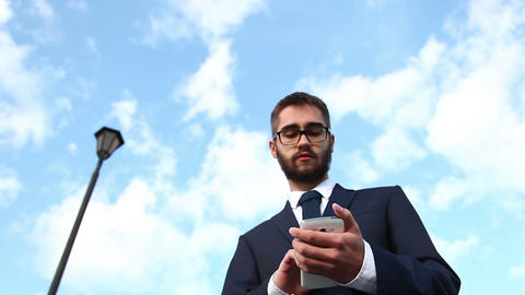 Businessman Talking On Mobile Phone. Bottom View. Dolly Shot stock footage