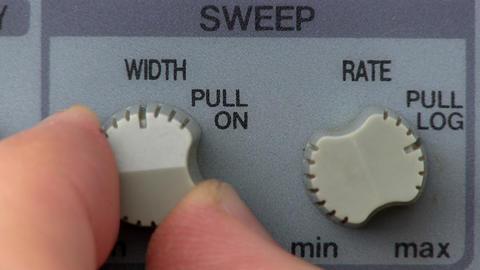 Dual knob turn; signal generator frequency sweep Footage