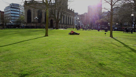 A man lying on the grass taking a rest in a public square Footage