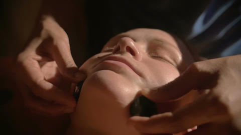 Relaxing facial massage with hot stones in beauty spa Footage