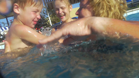 Boy and his family having fun in the pool Footage