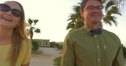 Happy young couple having enjoyable walk on tropical resort Live Action