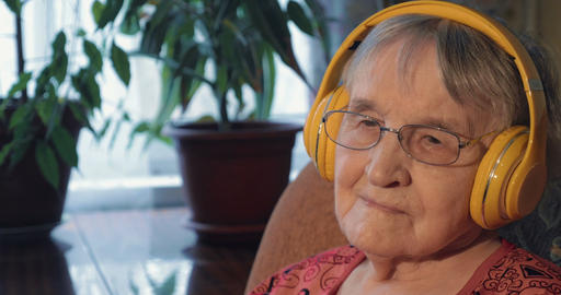 Senior Woman Listening to the Music in Headphones GIF