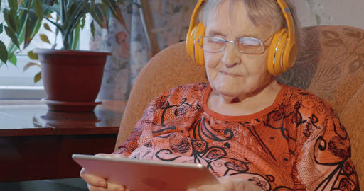 Grandmother using touch pad in wireless headphones Footage