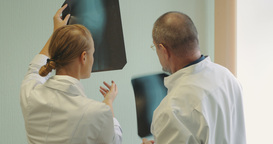 Male and female doctors examining x-ray images Footage