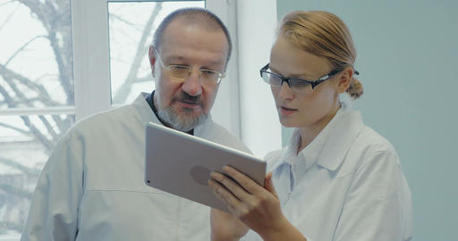 Two doctors having professional talk using touch pad Footage