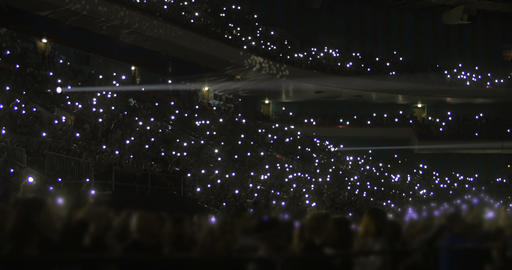 Crowd on stands waving flashlights at night Footage