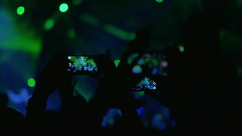 People with mobiles shooting laser show on the concert Footage