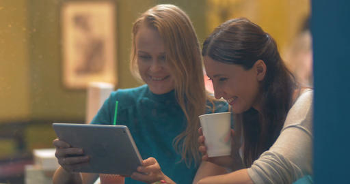Women in Cafe Laughing at Something in Tablet PC Footage